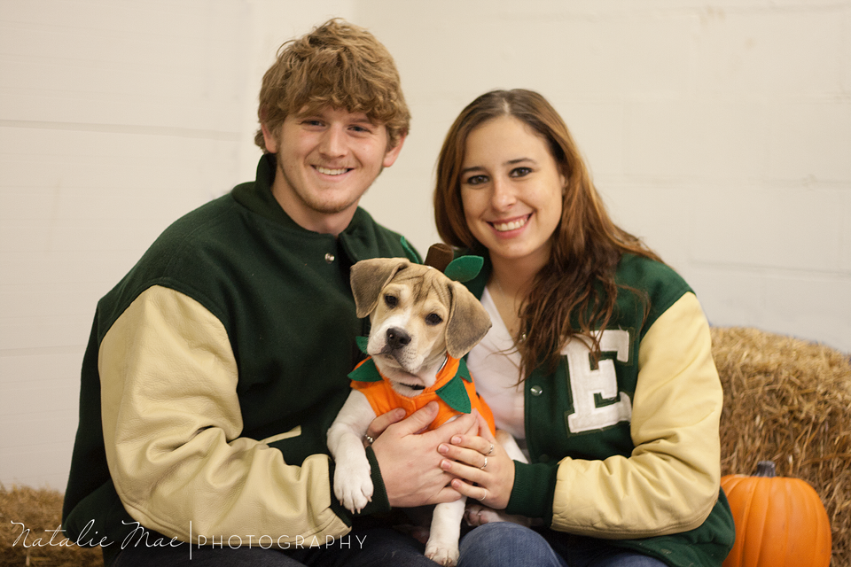 Two EMU students pose with their newly adopted puppy in a pumpkin costume during the Halloween pet photos